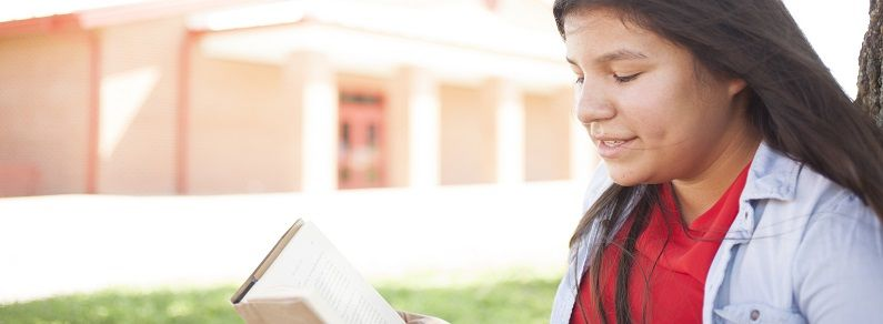 girl reading a book in front of a building